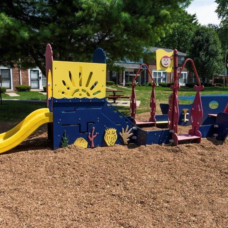 Blue, yellow, and red play gym for smaller children on light brown mulch